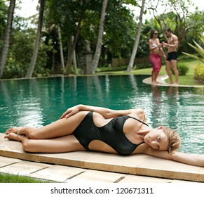 One woman and a couple lounging and relaxing by the edge of a swimming pool in a tropical destination hotel spa garden while on vacations.