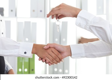 One woman is giving key to her client and shaking her hand in the company office. Concept of real estate purchasing