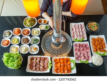 One woman grilling raw pork and chicken with red sauce ready to grill korean style, include slide food with vegetable, rice and soup in korean restaurant.