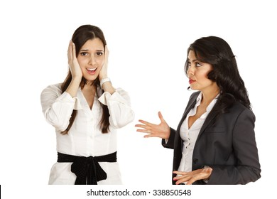 """One woman with her hands over her ears while being """"talked at"""" by another woman."""