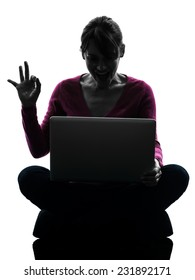 one  woman okay gesture computing laptop computer in silhouette studio isolated on white background
