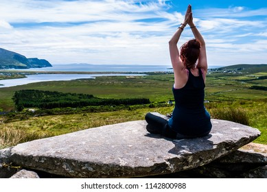 One woman performing some yoga stretches on top of the Megalithic Tomb on Slievemore on Achill Island in Ireland, with views of the Minaun cliffs and the ocean.