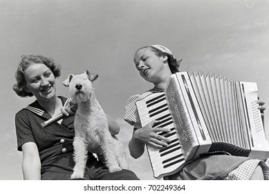 One woman playing accordion and another sitting with dog on her lap