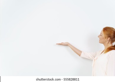One woman in a pretty blouse and with red hair extends hand with palm side up against a blank white board