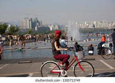 One woman is resting on a bicycle.Han River Park in Yeouido. Seoul city.South Korea
