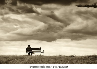 One woman sits on a bench and looks at the sea. Line horizon and earth on the background of beautiful clouds. Horizontal frame. Sepia