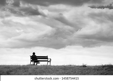 One woman sits on a bench and looks at the sea. Line horizon and earth on the background of beautiful clouds. Horizontal frame. Black and white image. High contrast