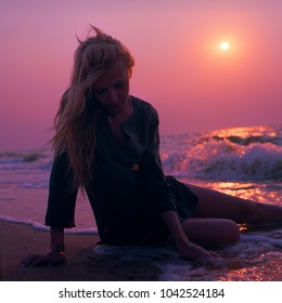 One woman sits on the sand a beautiful purple sunset in the sea