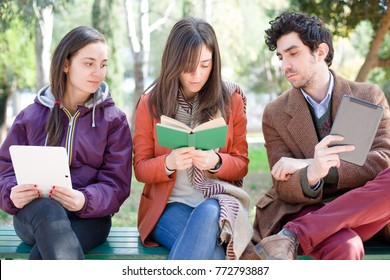One Woman Sitting on a Bench in a Park Reading a Paper Book with Two People with an E-Book Peeping