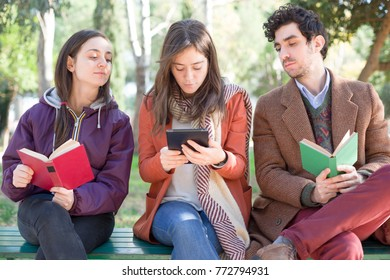One Woman Sitting on a Bench in a Park Reading an E-Book with Two People with Paper Books Peeping