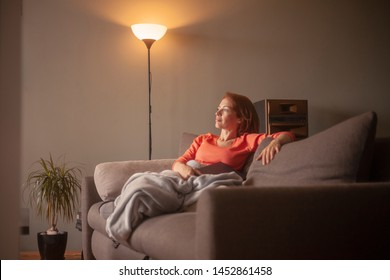 one woman, sitting in sofa, relaxing with a blanket and book in her hands. Joyful and looking away.