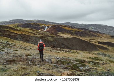 One woman traveler backpacker wanders in Iceland in red jacket