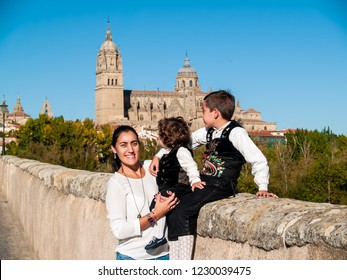 One woman and two children brothers embraced on the Roman bridge of Salamanca, dressed in traditional clothes and Salamanca cathedral