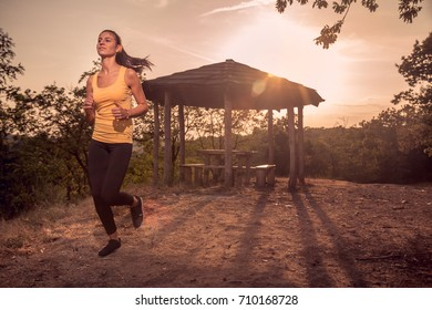 one woman young, running, sport clothes tights top, path, rural area,
