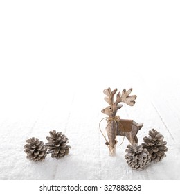 One wooden carved reindeer isolated on white snowy background for christmas decoration.