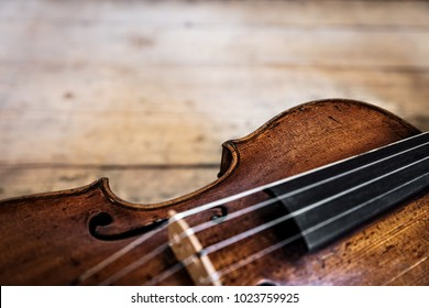 one wooden old fiddle on a rustic wooden background