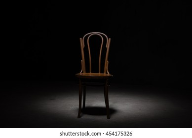 one wooden old retro chair in the dark room