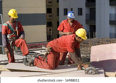 One worker is making a cut a on a sheet board with a circular saw.  Their are two other workers standing behind him.  Horizontally framed shot.