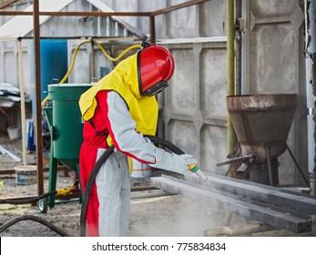 One worker. Surface preparation by sandblasting.