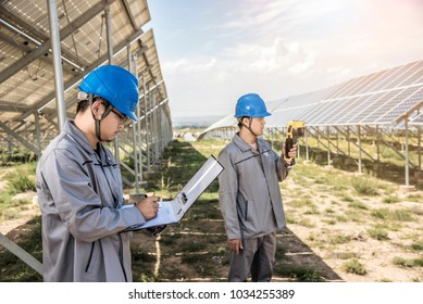 One worker is using the instrument to test solar PV panels and another worker is taking notes of the data