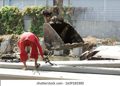 One worker working without safety shoes is unsafe workingplace. He is hooking stake with bucket for excavator to lift or move at construction site , wall is background.