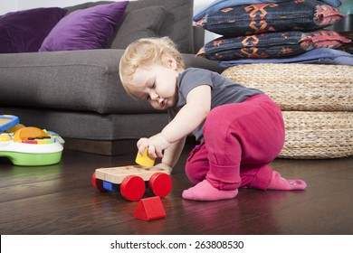 one year age blonde lovely cute caucasian white baby grey shirt pink trousers and shocks playing with wheel wooden colors toys indoor on brown floor