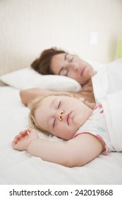 one year baby face and woman mother sleeping dreaming together in white quilt bed