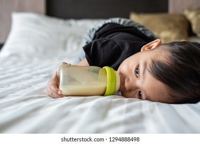 One year old baby boy lies in bed and drinks milk from a bottle. Baby, boy, mom, mother concept