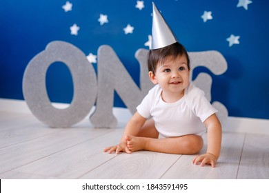 One year old baby boy in white t-shirt and silver hat celebrates birthday near silver letters ONE on purple background with stars.