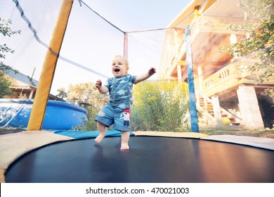 One year old baby boy jumping on trampoline. Happy little blond child with blue eyes jumping first time and having fun outdoor