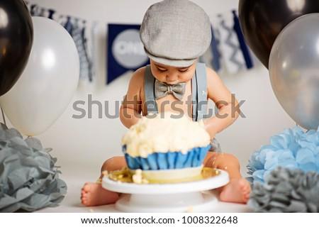 A One Year Old Baby Boy Smashing Blue Iced Birthday Cake On Silver Board