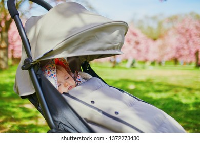 One year old baby girl sleeping in pushchair in park on a spring day