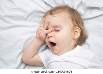 One year old baby girl boy wants to sleep, rubs his eyes with his hand and yawns on white sheets from above. Sleep training mode