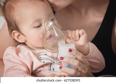 One year old baby girl inhaling from the inhaler, her mother holding her in the arms and comforting the ill baby, kissing her on the head