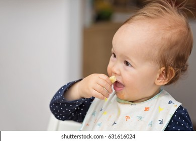 One year old baby girl feeding herself with her fingers, baby led weaning; concept of motherhood and parenting