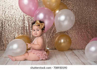 A one year old, baby girl sitting with a bunch of balloons. She is wearing pink bloomers, a gold, sequin headband and a string of pearls.