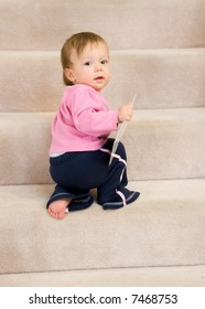 One year old baby girl climbing carpeted stairs.