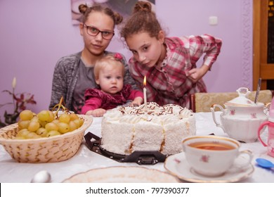 One year old baby girl with her sisters at the table in front of cake with a candle.