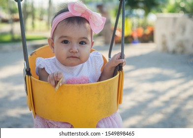 One year old baby, yellow swing and pink bow, a cookie in his hand, looks at a serious camera, unfocused background.