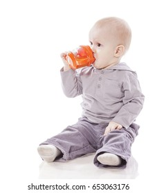 One year old boy drinking out of sippy cup isolated on white