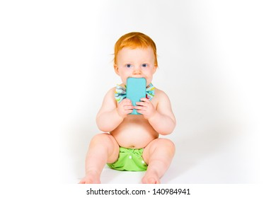 A one year old boy plays with a cell phone in the studio with a white background.