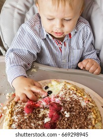 One year old boy is sitting in high chair and tasting his cake. First Birthday celebrating concept. Cake smash