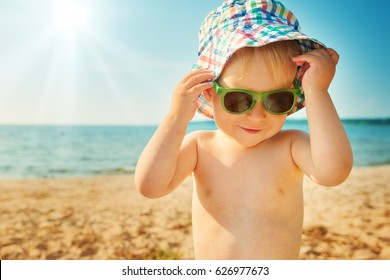 one year old boy smiling at the beach in hat with sunglasses. Child on vacations at sea