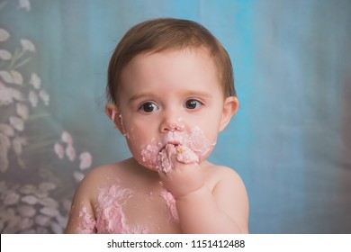 One year old caucasian girl celebrates her birthday with pink icing smash cake. Messy.
