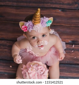 One year old caucasian girl wearing unicorn horn headband sits in front of pink smashcake with lots of frosting and icing