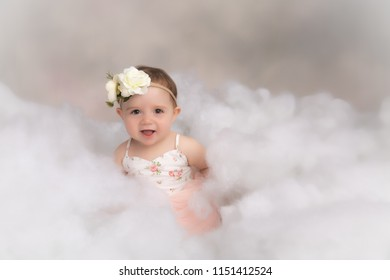 One year old caucasian girl in fluffy white cloud wearing floral dress and headband