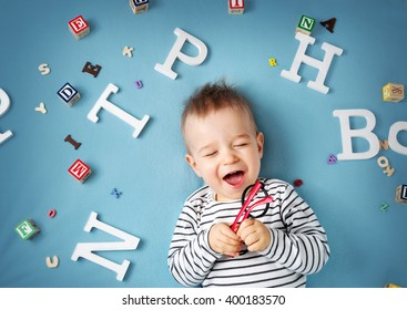 One year old child lying with spectacles and letters on blue background