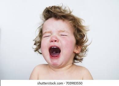 One year old girl crying with her mouth open and her eyes tight shut. Neutral background.
