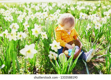 One year old girl playing egg hunt on Easter. Toddler sitting on the grass with many narcissi and gathering colorful eggs in basket. Little kid celebrating Easter outdoors in park or forest