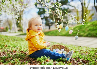 One year old girl playing egg hunt on Easter. Toddler sitting on the grass under apple tree in full bloom decorated with colorful eggs. Little kid celebrating Easter outdoors in park or forest